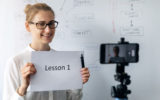 online education, webinar and business vlog concept - woman teaching and recording video with phone in front of whiteboard